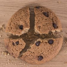 Image of close-up of a broken chocolate chip cookie on old wood
